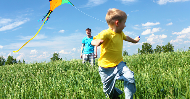 Father and son flying a kite, enjoying their stay at Riviera Oaks Resort